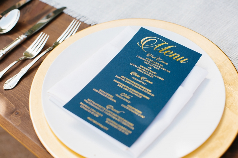 A photo of the navy blue and gold menu on the gold charger.