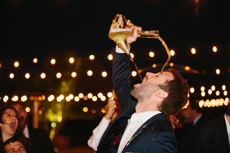 A groomsmen using the Spanish porron vessel and spilling it on his head.