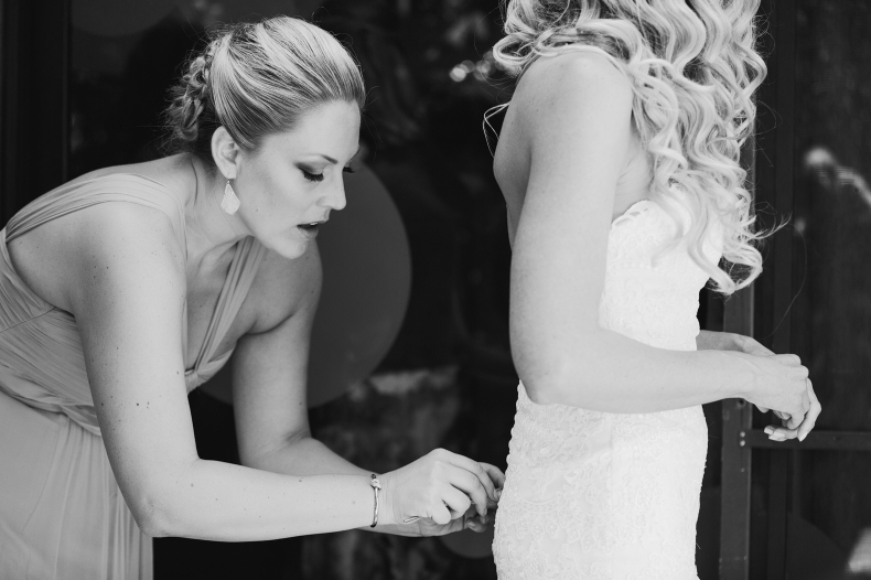 Here is a photo of a bridesmaid helping Sidney button her dress.