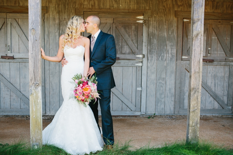 This is a photo of the couple kissing at the barn.