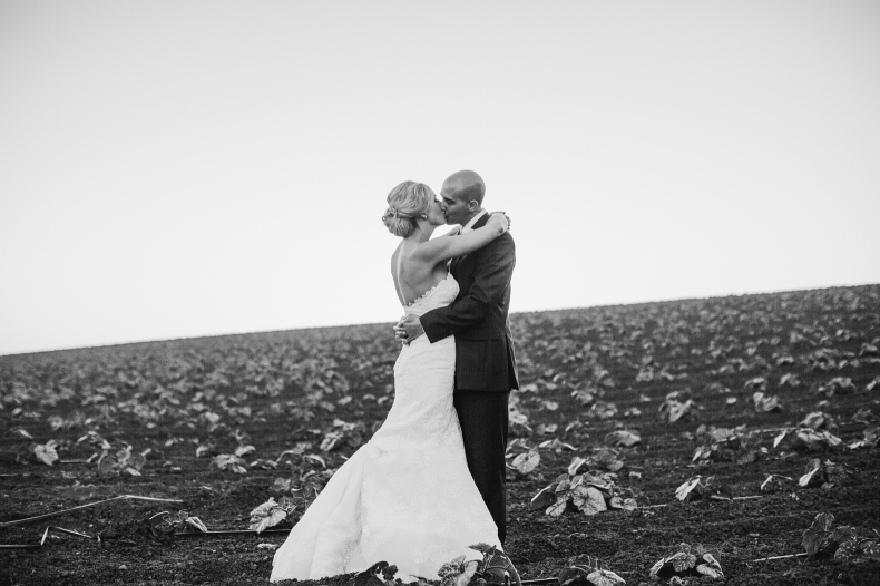 The bride and groom kissing in the fields behind Maravilla Gardens.