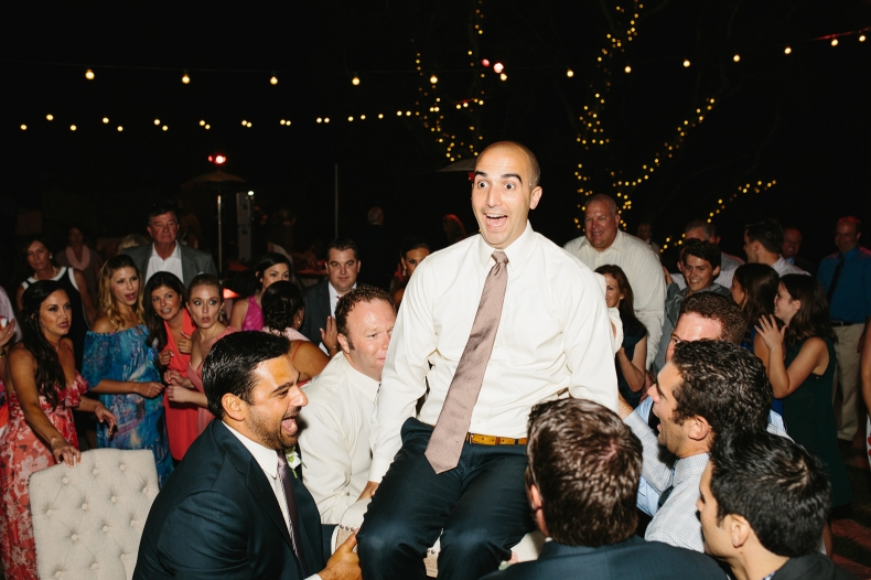 The guests lifted the groom on a chair.