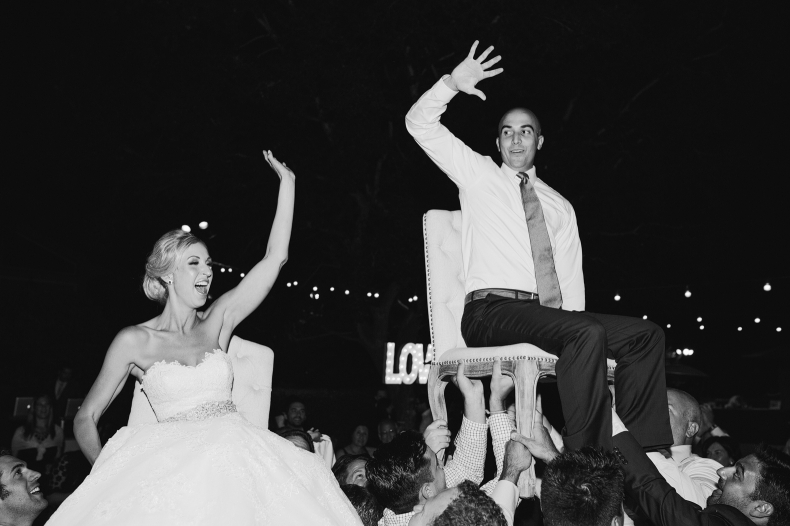 Here is a photo of the bride and groom during the reception being lifted on chairs.