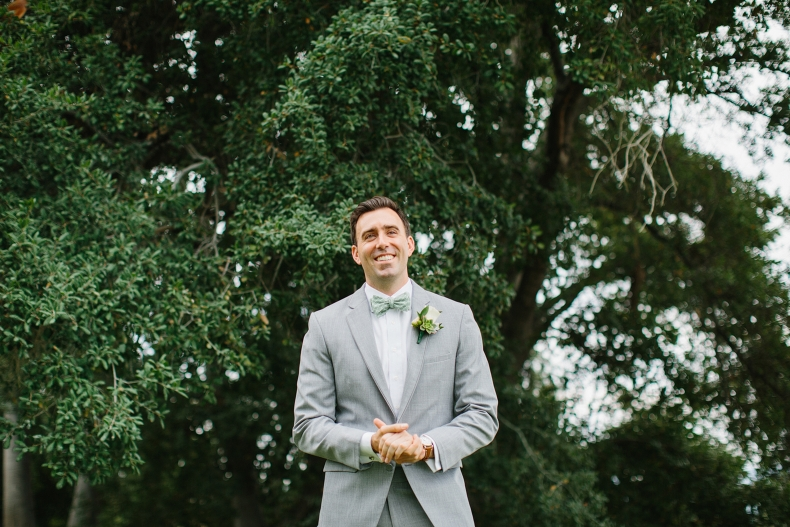 This is a photo of the groom in front of a large tree.