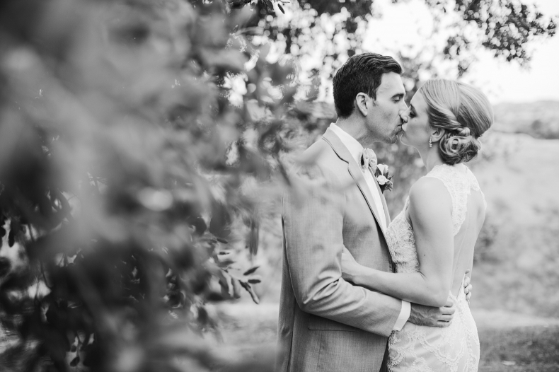 This is a black and white photo of the bride and groom kissing.