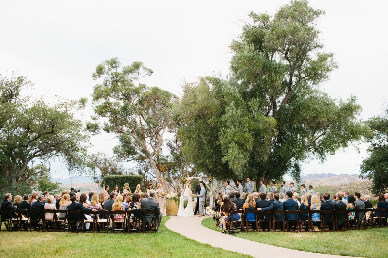 The ceremony was in front of large trees outside.