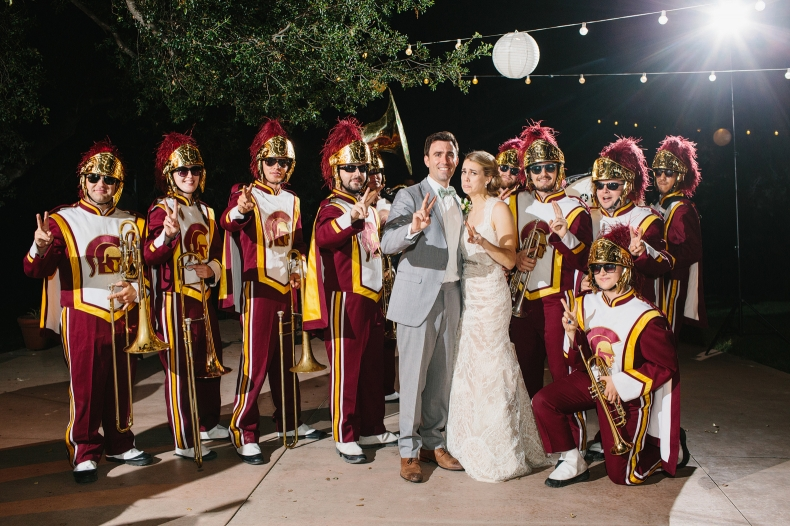 This is a photo of the bride and groom with the USC marching band.