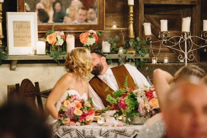 The bride and groom snuck a kiss during dinner.