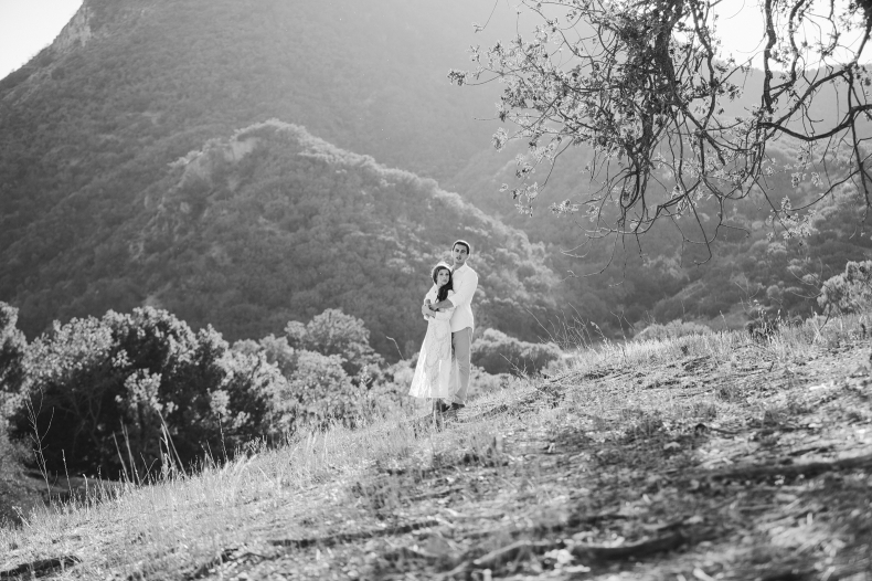 A black and white photo of the couple on the hillside.