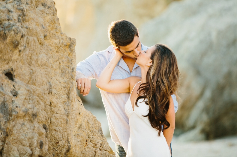 The couple kissing by a rock.