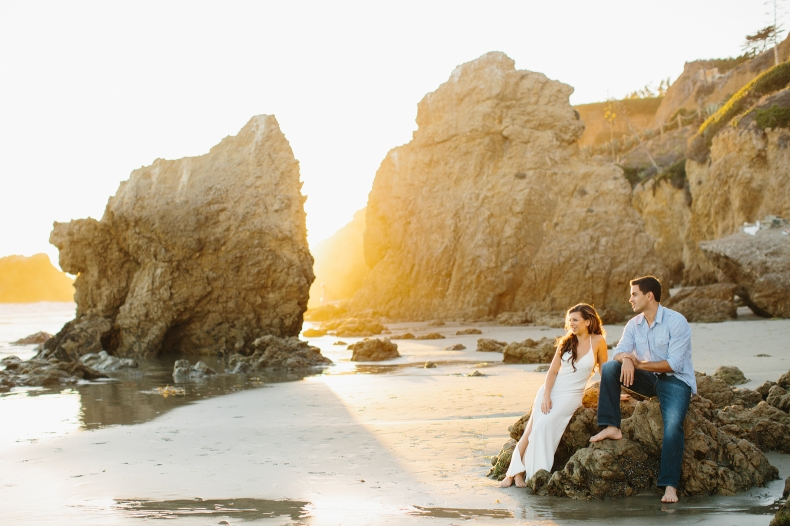 The couple sitting on rocks at the beach.