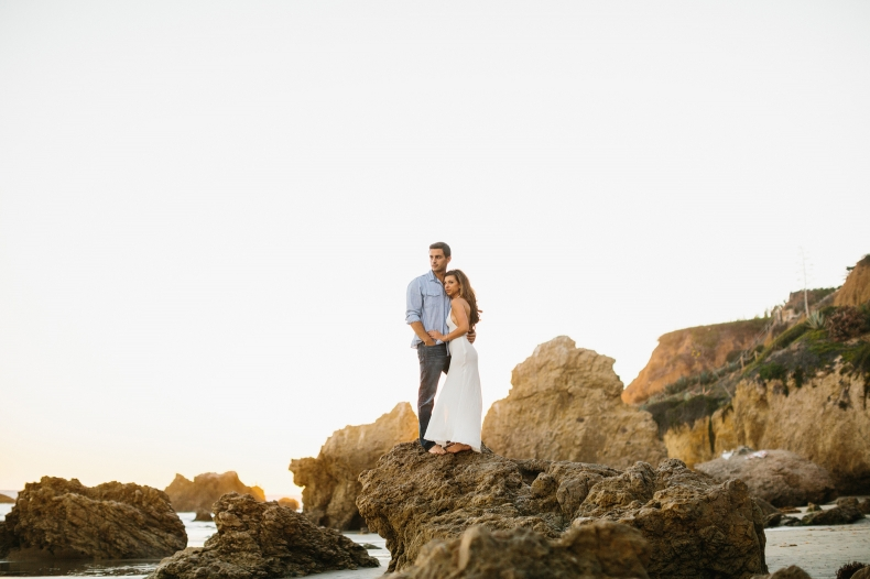 The couple standing on rocks.