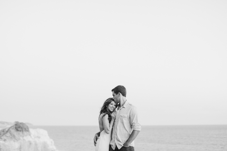A sweet black and white photo of Sara and Sam on the cliffside.