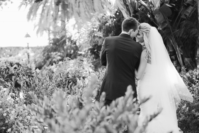 A beautiful black and white photo of the bride and groom walking.