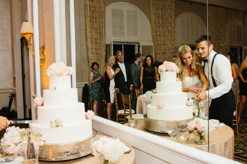 A cool shot of the bride and groom cutting the cake.