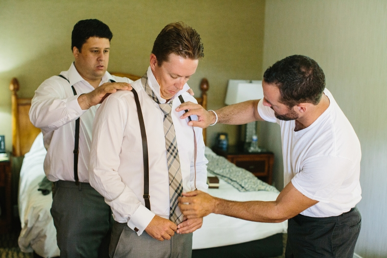 The groomsmen helping Chris put on his tie.