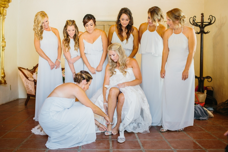 The bridemaids helped Liz put on her shoes.
