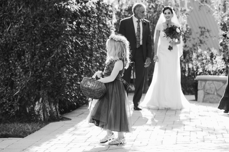 The flower girl walking down the aisle.
