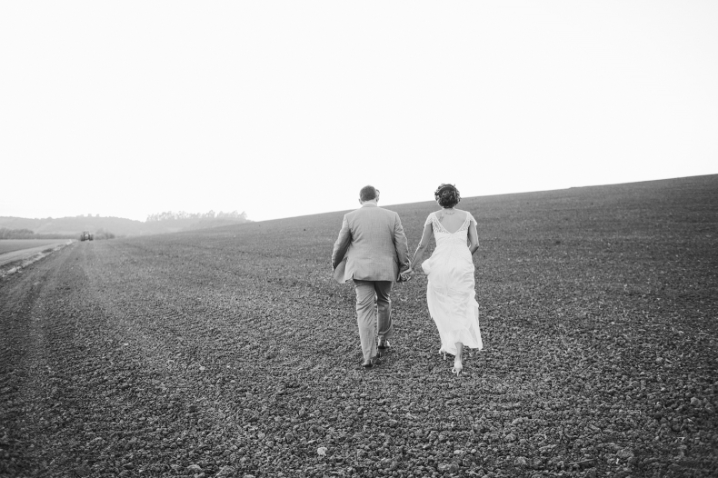The couple walking in the fields.