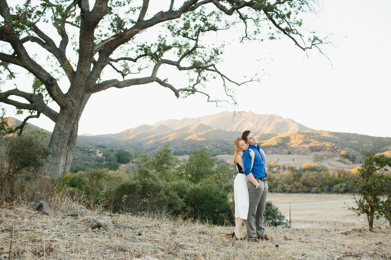 A sweet photo of the couple with hills in the background.