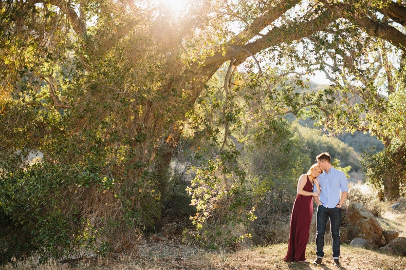 The couple standing under a large tree in the Malibu Hills.