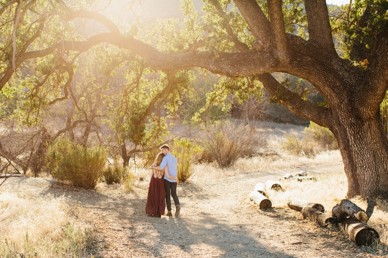 The couple walking under a large tree.