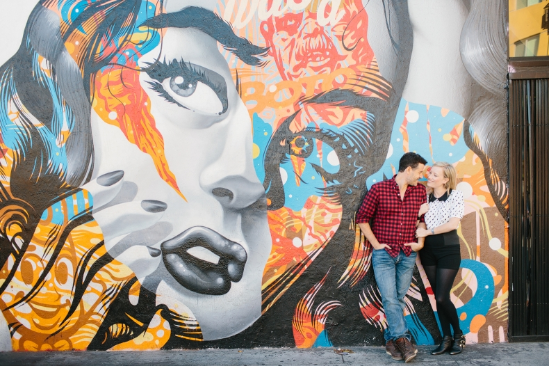 The couple in front of a graffiti wall.