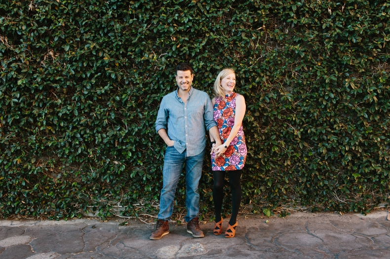 Hayley and David in front of a wall covered in green plants.