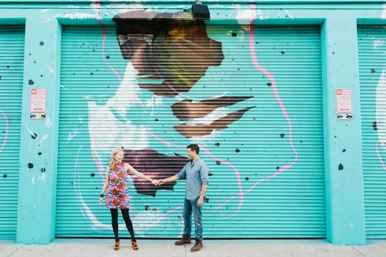 Hayley and David dancing in front of a teal mural.