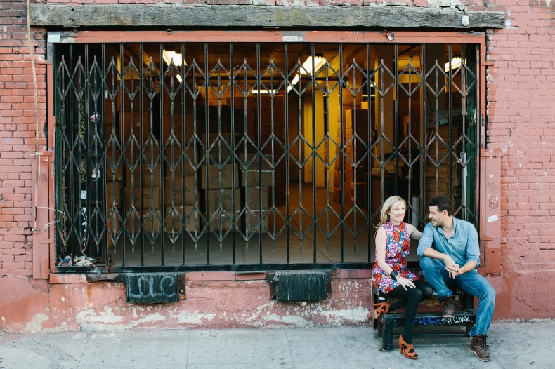 The couple sitting in front of a warehouse.