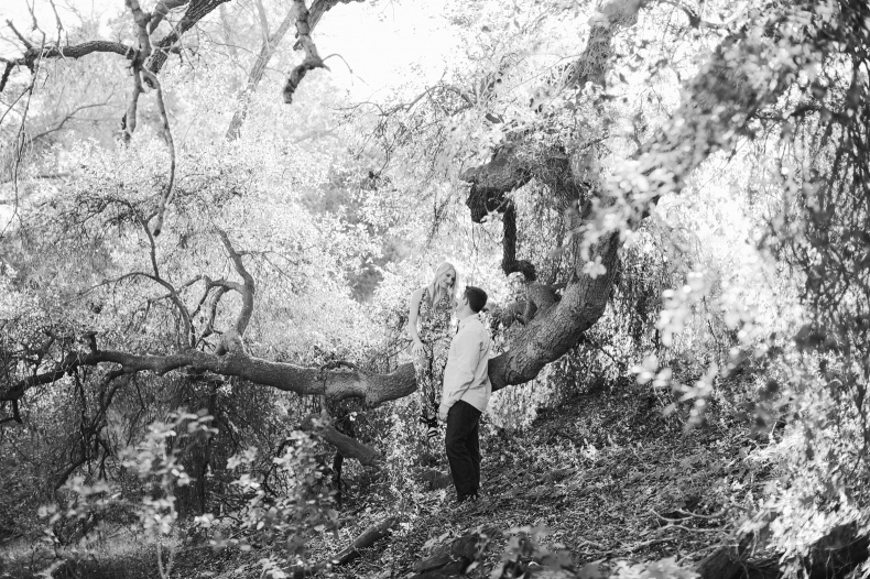 A black and white photo of the couple in the trees.