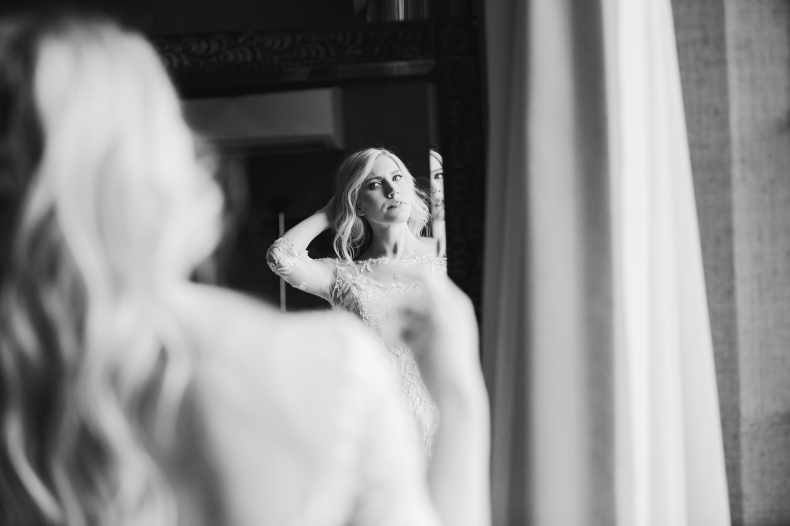 The bride fixing her hair in the mirror.