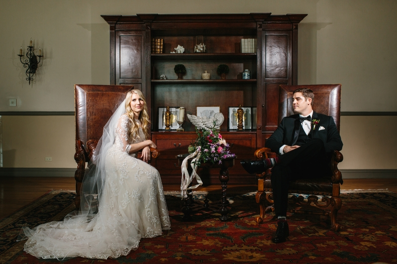 The bride and groom sitting in two leather chairs.