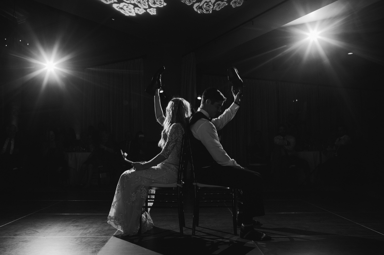 A cool black and white photo of the bride and groom lifting their shoes.