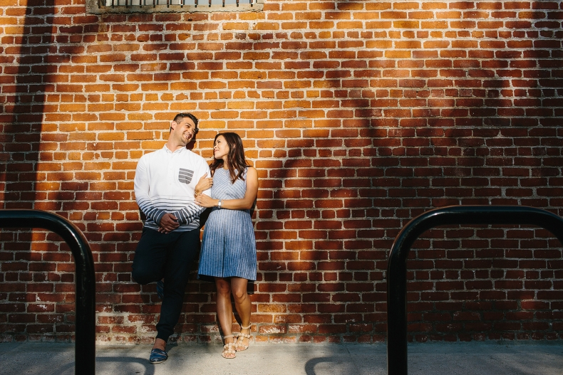 The engaged couple in front of a brick wall.