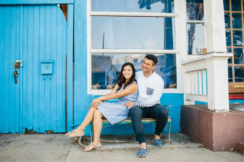 The couple in front of a blue building.