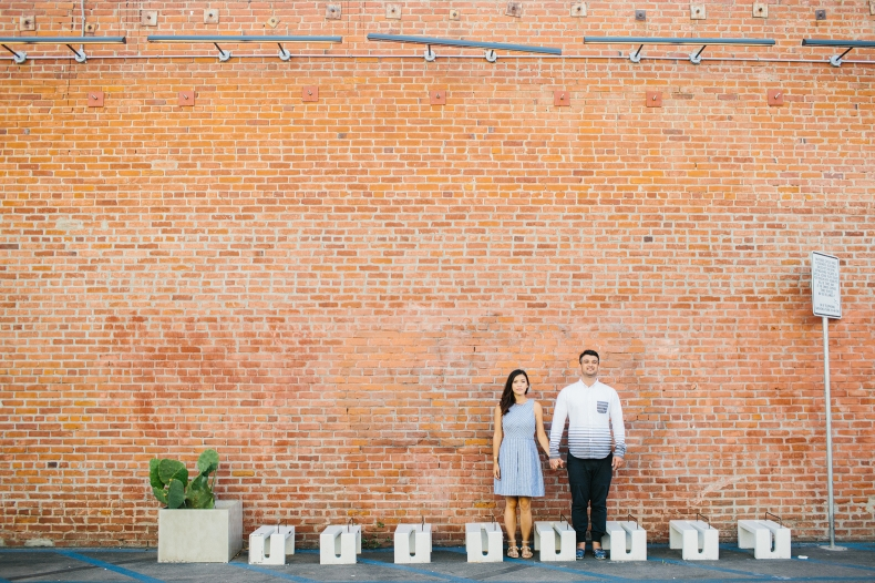 The couple by a brick building.