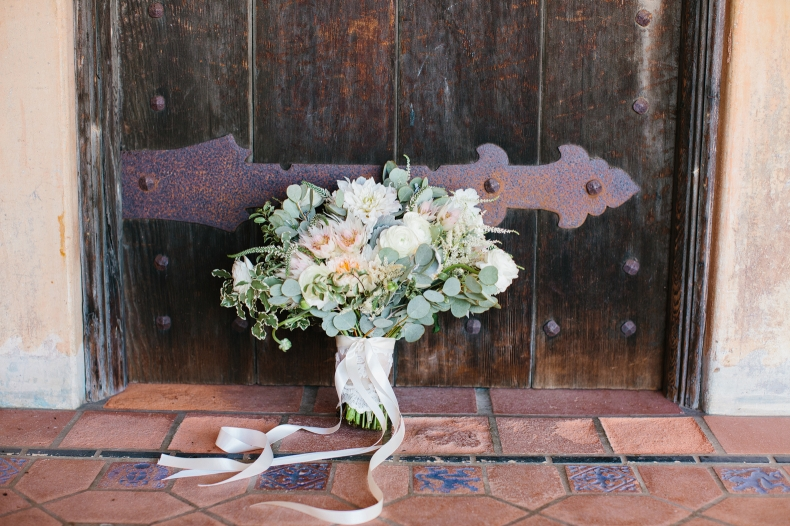 The bridal bouquet against a wood door.