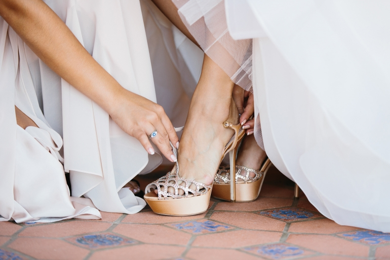 A bridesmaid helping Maily get in her shoes.