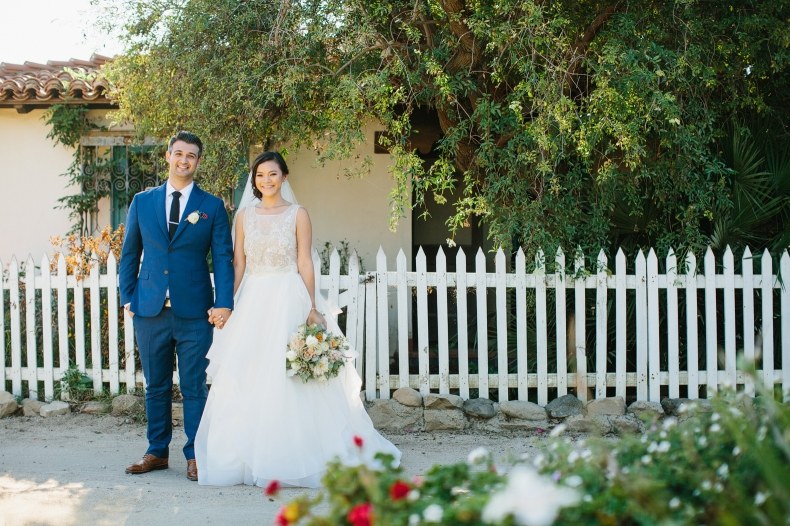The couple in front of a picket fence.