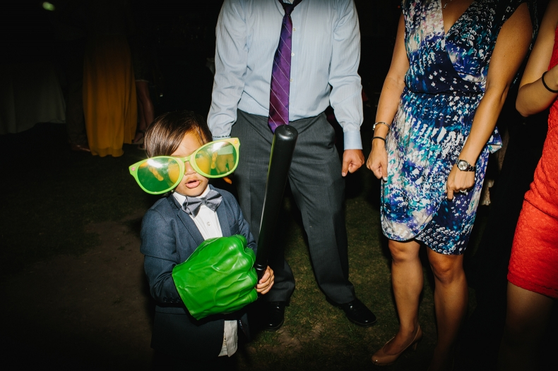 The ring bearer playing with photobooth props.