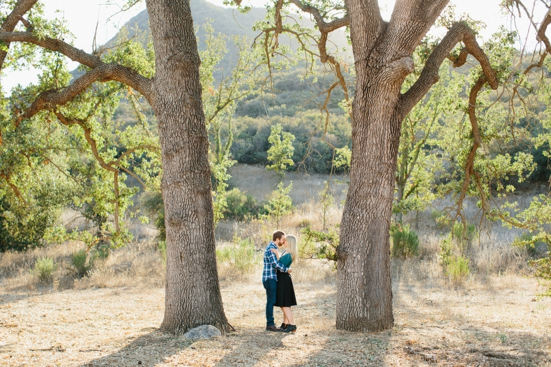 Th couple standing between two large trees.