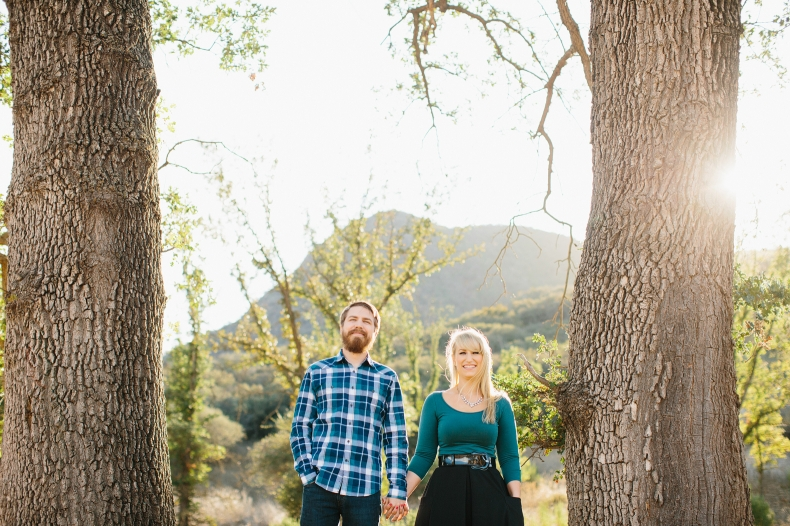 Lindsay and Josh standing between two trees.
