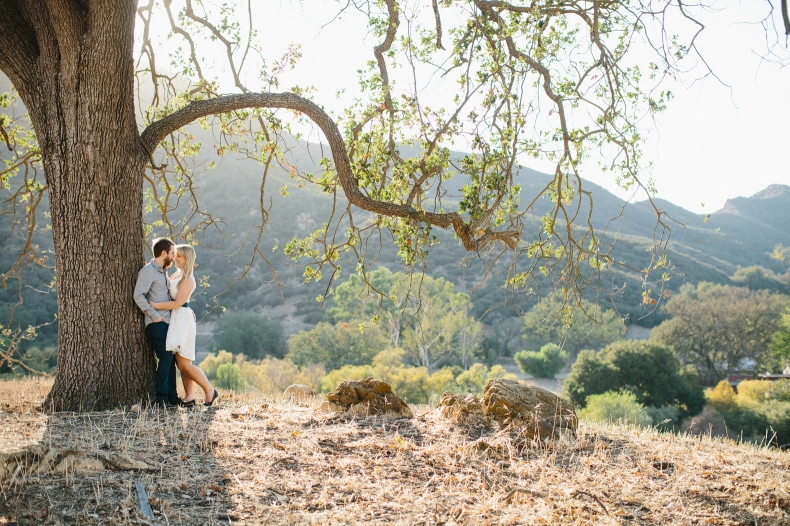 The couple leaning on a tree.