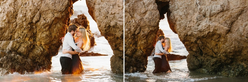 The couple stnading in water under a rock.