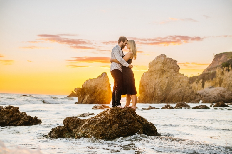 The couple on a rock surrounded by water.
