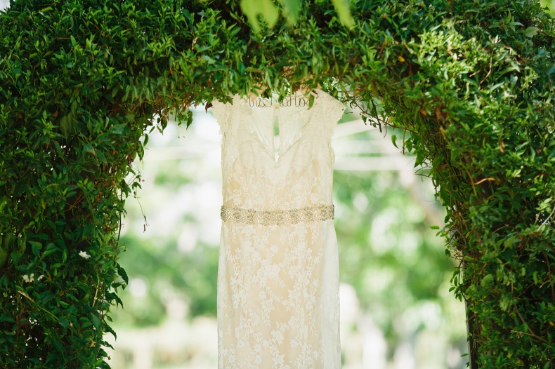 The wedding dress hanging in an arch.